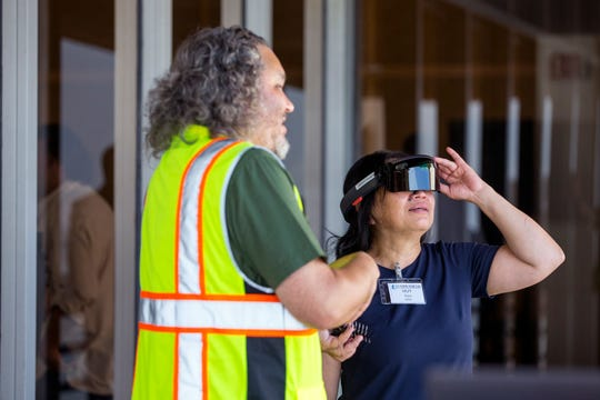 Kenji Kato, left, with NASA Ames, gives Huy Tran, from left, NASA Ames Director of Aeronautics, a look at augmented reality glasses being used to test human factor concepts within the NASA Unmanned Aircraft Systems Air Traffic Management software tests in Corpus Christi, TX, on Thursday, August 15, 2019.
