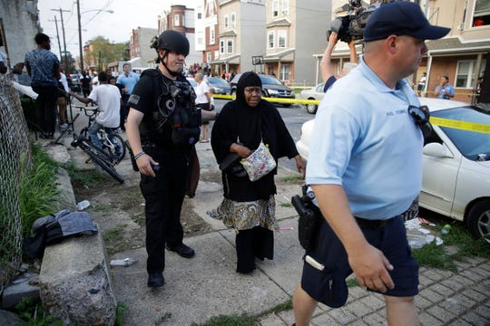 Police officers escort a bystander away from the scene of a shooting, Wednesday, Aug. 14, 2019, in the Nicetown neighborhood of Philadelphia.