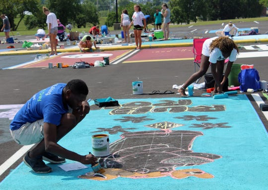 Zaria Black used a Scooby-Doo theme for her parking space at Fairfield Senior High School. Assisting her in the painting is her father, Joseph.