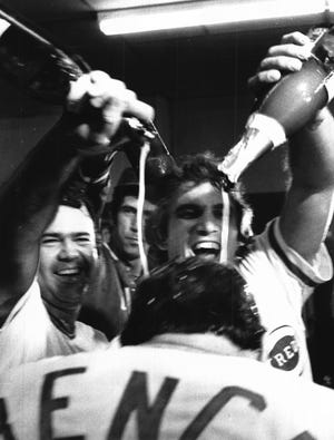 Bob Bailey and Bill Plummer douse Johnny Bench with champagne in the clubhouse after beating the Phillies in the NLCS. Between Bailey and Plummer, Pat Zachry is visible.