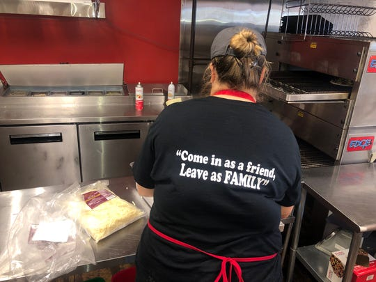 "Caprigios employee, Faith Willis wears shirt with their slogan, "" Come in as a friend, leave as family."""
