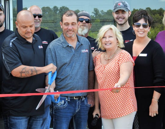 Brothers Brian and Ron Wahl cut a ribbon for the new location of J&R Door with Amy Stockdale of the Coshocton County Chamber of Commerce, Tiffany Swigert of the Coshocton Port Authority and other local officials and employees of the business.