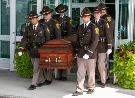An Oakland County Sheriff's honor guard carries the coffin of L. Brooks Patterson out of Woodside Bible Church in Troy on Thursday.