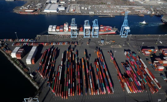 In this March 5, 2019, file photo, cargo containers are staged near cranes at the Port of Tacoma, in Tacoma, Wash.