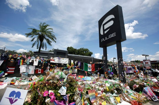 In this July 11, 2016, file photo, a makeshift memorial continues to grow outside the Pulse nightclub in Orlando, the day before the one month anniversary of a mass shooting, in Orlando, Fla.