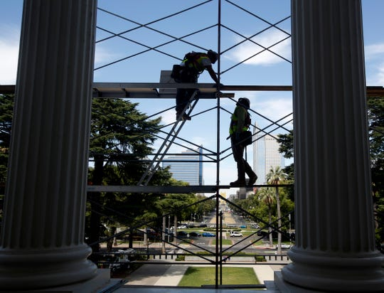 FILE - In this July 25, 2019, file photo workers assemble scaffolding on the west side of the state Capitol in preparation for a routine maintenance project, in Sacramento, Calif.  Yields on 2-year and 10-year Treasury notes inverted early Wednesday, Aug. 14, a market phenomenon that shows investors want more in return for short-term government bonds than they do for long-term bonds. It's the first time that has happened since the Great Recession and it can be a sign that investors have lost faith in the soundness of the U.S. economy.