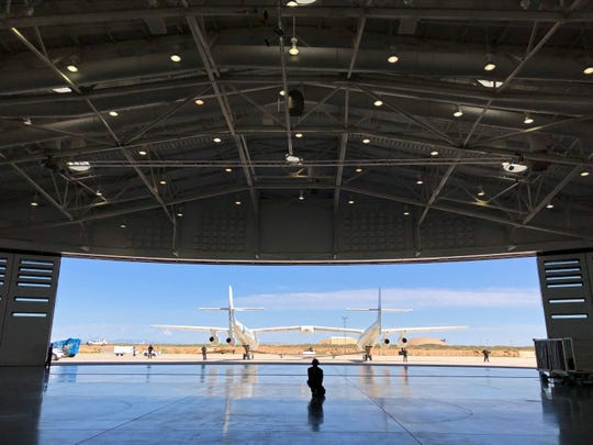 Virgin Galactic ground crew guide the company's carrier plane into the hangar at Spaceport America following a test flight over the desert near Upham, New Mexico, on Thursday, Aug. 15, 2019. The carrier plane is now permanently based at the spaceport after arriving earlier this week.