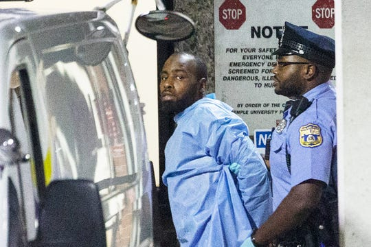 Police take shooting suspect Maurice Hill into custody after an hourslong standoff that wounded several police officers in Philadelphia early Thursday, Aug. 15, 2019.