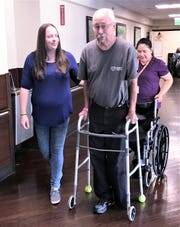 Physical therapy assistant Amber White helps Elmira resident Richard Merchant, who recently had part of his left leg amputated, learn to walk again at the Corning Center for Rehabilitation and Healthcare.
