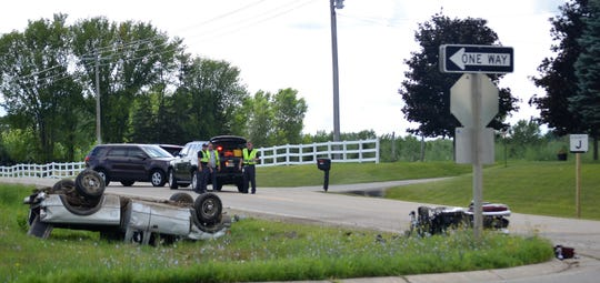 An overturned pickup and a motorcycle  are seen  after they collided on Oconto County J along Highway 41 south of Oconto on Wednesday. The motorcyclist died. Looking on are officers of the Oconto County Sheriff's Office and the Wisconsin State Patrol.