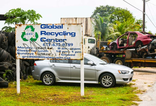 A tractor hauls a trailer loaded with junk cars into the gates of the Global Recycling Center, along Bartolu Street in Dededo, in this Aug. 15 file photo.