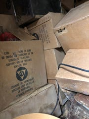 Cardboard boxes that contained tins of survival crackers and other emergency supplies from the early 1960s lay strewn in a locked crawlspace in the basement of South Middle School. Samples of supplies for a basement fallout shelter have been donated to the Henderson County Historical and Genealogical Society for preservation.