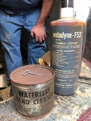 "A rusty can of waterless hand cleaner and a bottle of ""tamed"" iodine are among the remnants of survival kits that were once stocked in the basement fallout shelter at what is now South Middle School. (Photo by Chuck Stinnett)"