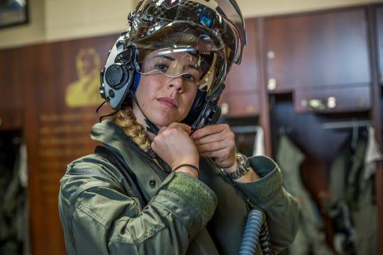 Capt. Anneliese Satz puts on her flight helmet prior to a training flight.