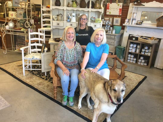 Sisters (seated) Mary Ann Miller (left) and Martha Dooley have developed a business, The Painted Woods, with Eve Kiser and mascot Belle.
