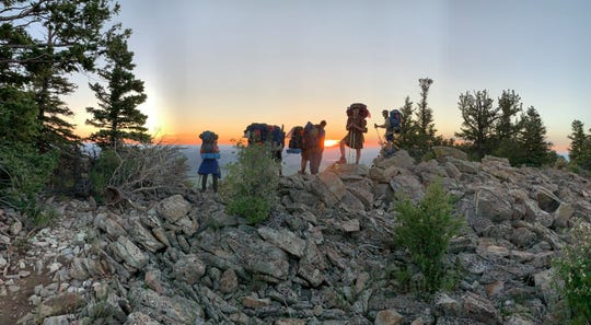 Spencer Berry takes a pause while hiking a rocky ridge with fellow scouts at sunrise at Philmont Scout Ranch in Cimarron, N.M., in June.