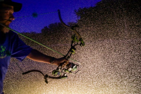 Millions of bugs fly around the boats lights as Gene Mills looks for a fish to fire towards, Wednesday, Aug. 14, 2019 on the Tippecanoe River.