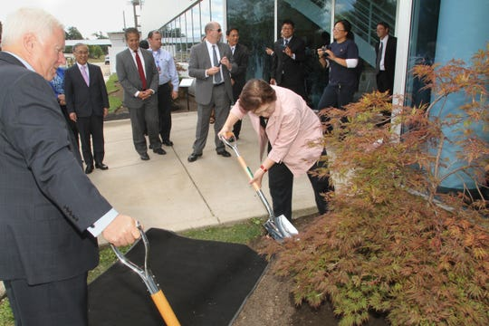 Howell Mayor Nick Proctor, left, assists as Thai Summit Group President Dr. Somporn Juangroongruangkit performs a ceremonial planting of a tree in front of the Thai Summit offices in Howell in this August 2015 photograph.  The planting of two trees was intended to symbolize the growing Livingston County presence of Thai Summit America Corporation.