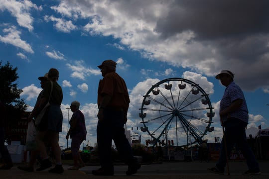 Attendees make their way through the food options alongside the midway at the Kentucky State Fair on Aug. 15.