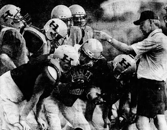 Haslett football coach Tom Motherwell gives instructions to his team during the 1990 season.