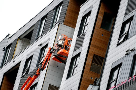 A man works up high around the windows of The Landmark apartment building on Thursday, Aug. 15, 2019, in East Lansing.