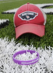 A wrist band remembering Manitowoc Lincoln football coach John Dixon rests on the artificial turf in this illustration at Ron Rubick Field Aug. 13.