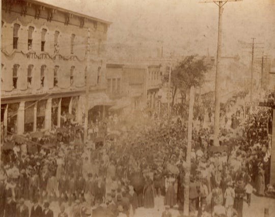 Crowd and parade of Company H on South Eighth Street in Manitowoc, in front of Williams House, after Spanish-American War.