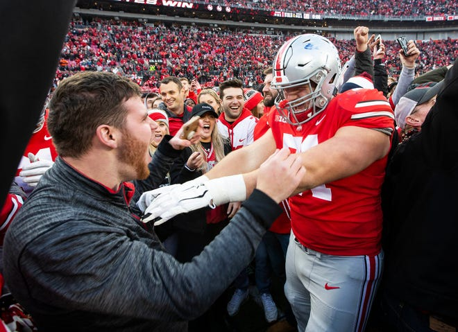 Ohio State offensive lineman Josh Myers celebrates with fans after last season's win at home over Michigan.