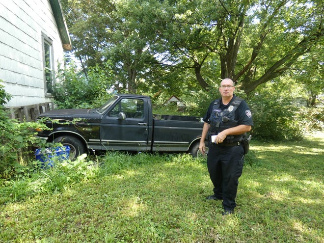 Marion Police Officer Casey Thomas checks on a junk motor vehicle complaint on Cherry Street. How the city handles nuisance complaints and housing issues has become a central issue of the Marion mayoral race.