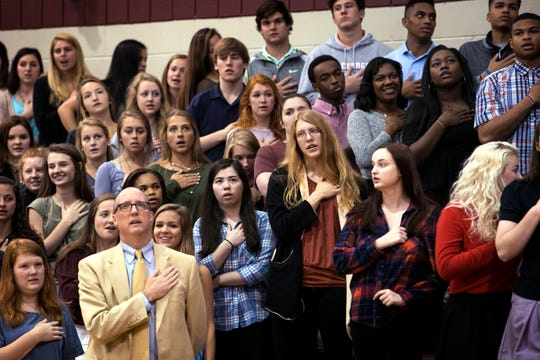 St. George's students, along with form Head of School Ross Peters (bottom, left), say the Pledge of Allegiance before the start of an upper-school chapel service in the school's gym on May 9, 2016.