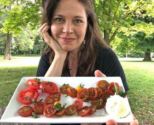 "Melanie Manuel of Celesta restaurant shows her caprese salad, served with ricotta ""cheese"" made with almonds."