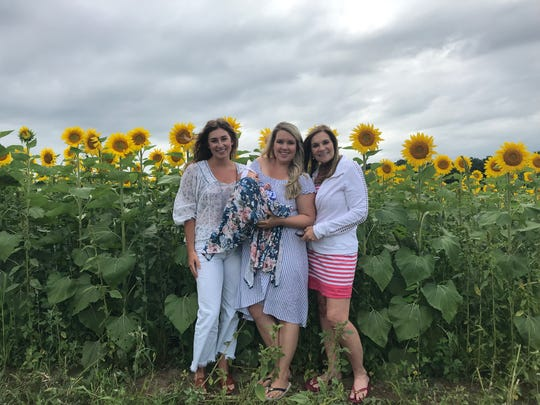 Olivia Juhl, left, Alisa Koch, holding her 2-month old daughter, Vivian, and Lisa Droegkamp pose in front of the sunflowers next to Stone Bank School on Wednesday, Aug. 14, 2019.