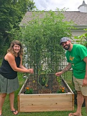 Calley and Michael Hostad check on some of the tomato plants they grow in their backyard in Fox Point.