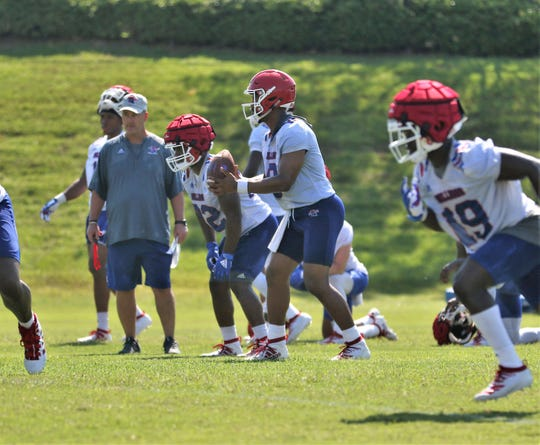 Louisiana Tech redshirt senior quarterback J'Mar Smith (8)  runs a play during practice with offensive coordinator and quarterbacks coach Todd Fitch, left, looking on.