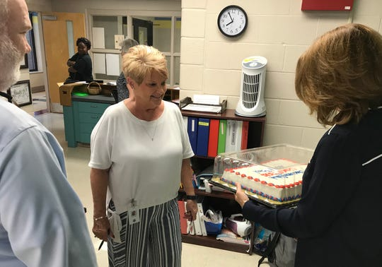 Lana Hogin, The Discovery School secretary, checks out the cake given to the school by county education administrators Wednesday for being a Level 5 TNReady school.