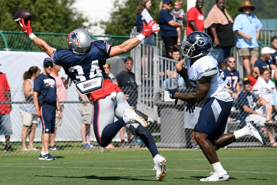 New England Patriots running back Rex Burkhead (34) drops a pass as he is defended by Tennessee Titans linebacker Daren Bates (53) during a joint training camp practice at Saint Thomas Sports Park Thursday, Aug. 15, 2019 in Nashville, Tenn.