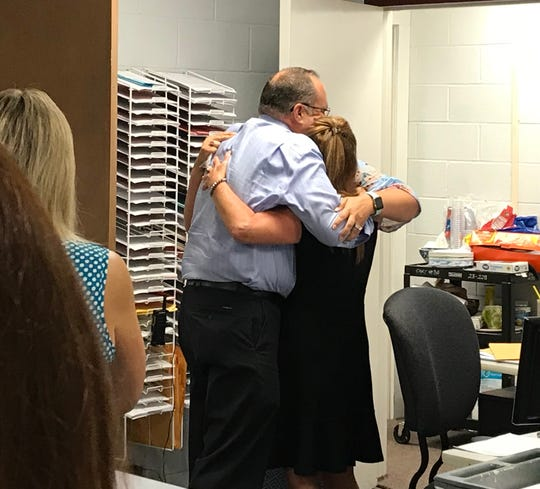 Former Dickson Middle School principal Dr. Woody Burton hugs current Principal Leslie Harrison and Vice Principal Hubbell Purvis after the school earned a Level 5 designation.