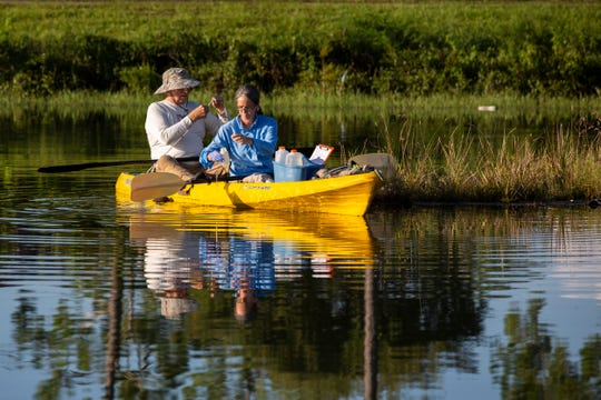 Kamila Perez, right, a senior environmental specialist with Collier County, and Duke Vasey, left, a volunteer of the Florida Lakewatch project, sample water at a pond by Collier Boulevard on Friday, July 19, 2019, in Golden Gate Estates.