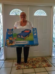 Cynthia Shafer shows a toddler bed donation