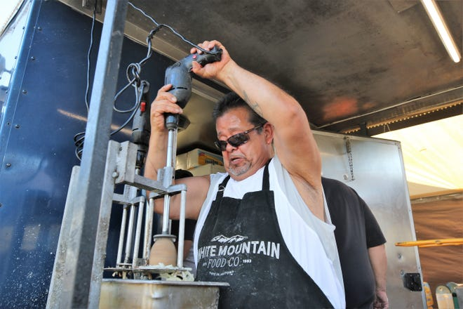 Raymond Valencio of White Mountain Food Co. starts the process of making curly fries at the San Juan County Fair at McGee Park on Aug. 13.