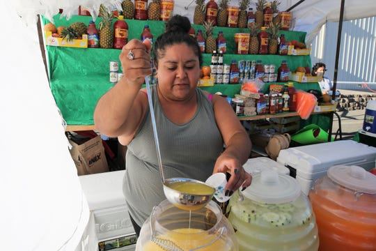 Izuri Garcia of the Las Comadres food stand prepares a sample of pineapple lemonade at the San Juan County Fair at McGee Park on Aug. 13.