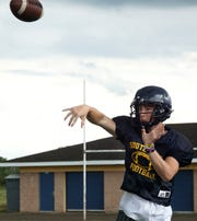South Lyon High football player Connor Fracassi tosses a pass during a practice on Aug. 15.