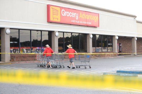 Grocery Advantage employees remove carts from the parking lot outside the store Aug. 15, 2019, after a suspect who fired shots inside the store was shot by an Escambia County Sheriff's Office deputy.