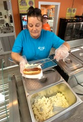 Jeanette McClain starts the creation of a Wacky Macky hot dog,  at Wacked Out Weiner in Milton on Thursday, Aug. 15, 2019. The new eatery is scheduled to open on Friday, Aug. 16, 2019.