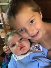 Jacob holds his baby brother Joshua.