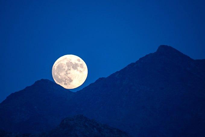 Near full moon rising over the Estrella Mountains as seen from Buckeye.