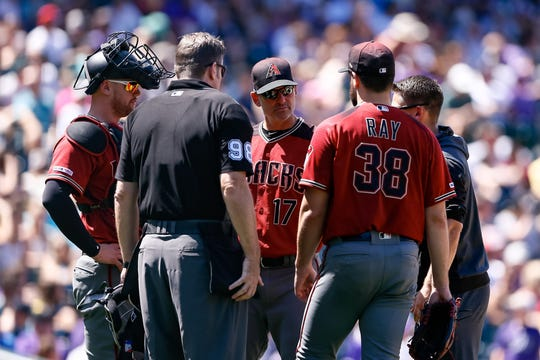 Aug 14, 2019: Arizona Diamondbacks manager Torey Lovullo (17) visits the mound with catcher Carson Kelly (18) to talk to starting pitcher Robbie Ray (38) as home plate umpire umpire Chris Conroy (98) looks on in the third inning against the Colorado Rockies at Coors Field.