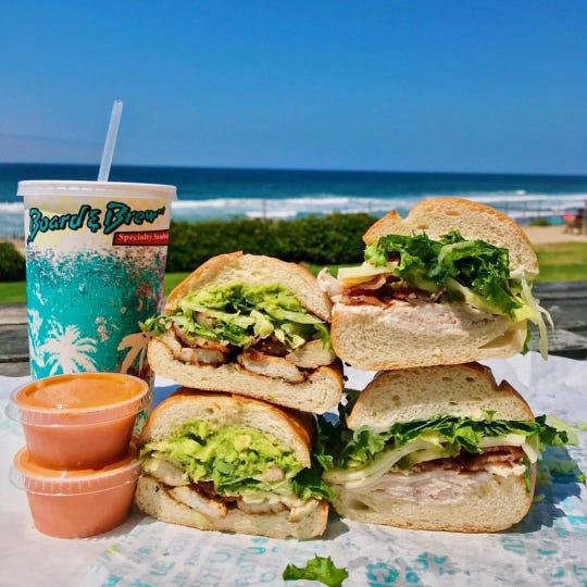 Sandwiches from Board and Brew are laid out in front of a beach. The sandwich shop chain offers a secret sauce for its sandwiches.