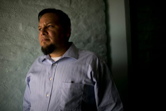 Immigration attorney Ruben Reyes looks out of his office windows in Phoenix on Aug. 9, 2019.