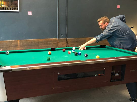 Scott Church casually shoots a game of pool in between chatting about the future of his hometown, Lebanon.